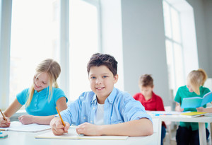 Portrait of diligent pupils drawing at lesson in classroom