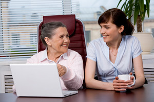 Portrait of elderly woman consulting her pretty granddaughter what to type