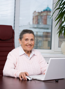 Portrait of elderly woman looking at camera during computer work in office