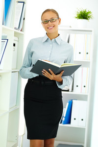 Portrait of elegant businesswoman with notepad looking at camera in office