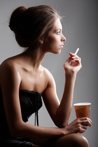 Portrait of elegant female smoking with plastic glass in hand