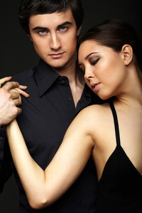 Portrait of elegant girl with handsome man looking at camera on black background