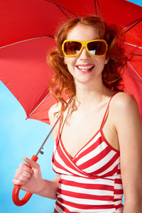 Portrait of elegant woman in sunglasses under umbrella