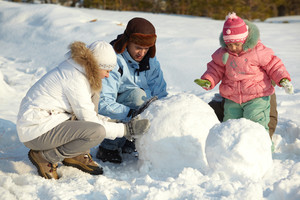 Portrait of family making snowman in park