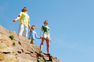 Portrait of family members standing on cliff with stretched arms and enjoying hot day