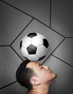 Portrait of footballer balancing a ball on his head