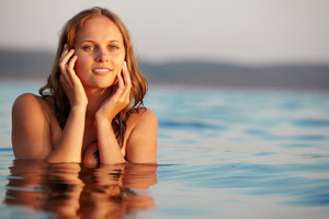 Portrait of fresh young girl in water posing before camera at summer