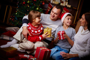 Portrait of friendly family with gifts spending Christmas evening at home