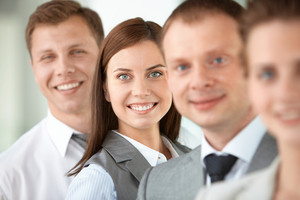 Portrait of friendly leader looking at camera between employees