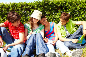 Portrait of friendly teens sitting on green grass and interacting
