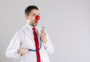 Portrait of funny doctor with red nose
