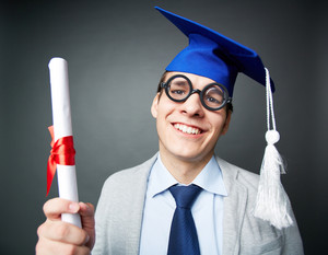 Portrait of funny student in eyeglasses holding graduation certificate and looking at camera