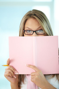 Portrait of girl in eyeglasses peeping out of notepad
