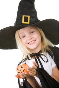 Portrait of girl in witch costume and small pumpkin in hands looking at camera