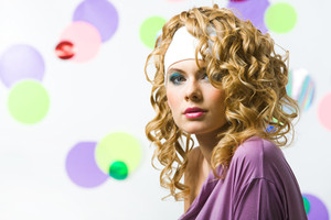 Portrait of glamorous blonde with wavy hair-style looking at camera on colorful background