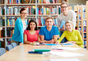 Portrait of group of students sitting in college library and doing homework