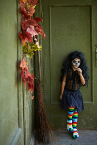 Portrait of Halloween girl with broom on background of wall of dilapidated house