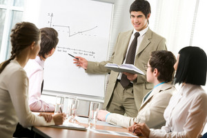 Portrait of handsome businessman pointing at graph on board and looking at his co-workers with smile