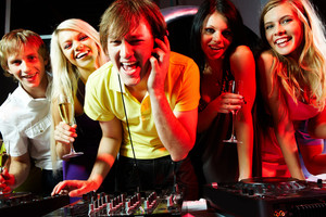 Portrait of handsome deejay singing with joyful friends near by