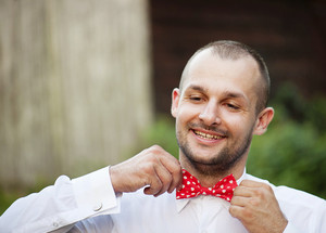 Portrait of handsome groom in the park getting ready for the wedding.