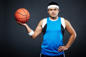 Portrait of handsome guy in sportswear holding basket ball and looking at camera