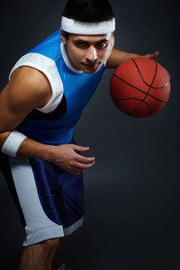 Portrait of handsome guy in sportswear playing basket ball