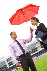 Portrait of handsome man holding red umbrella above female head