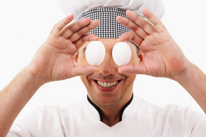Portrait of handsome man in cook uniform holding two eggs in front of his eyes