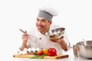 Portrait of handsome man in cook uniform smiling at camera during work