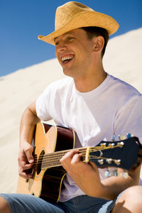 Portrait of handsome man in cowboy hat playing the guitar and singing something on sunny day