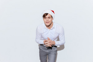 Portrait of handsome young businessman in santa claus hat standing over white background