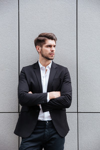 Portrait of handsome young businessman standing with hands folded