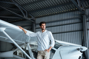 Portrait of handsome young man standing near smal airplane