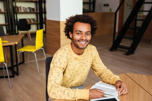 Portrait of happy african american young man sitting and studying in library