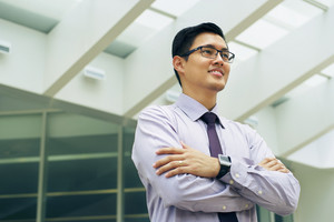 Portrait of happy and confident young asian businessman. The man stands in a street against office buildings and crosses arms looking away