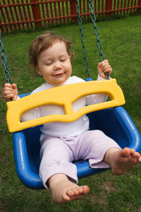Portrait of happy baby swinging during summer vacations and enjoying it