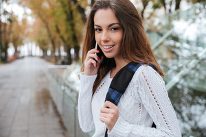 Portrait of happy beautiful young woman standing and talking on mobile phone in park