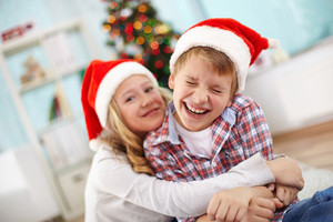 Portrait of happy boy laughing in his sister embrace on Christmas evening