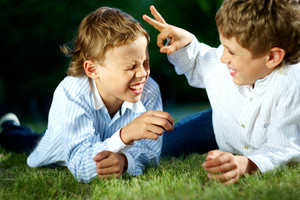 Portrait of happy boys playing jokes on grass in park