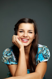 Portrait of happy brunette looking at camera over grey background