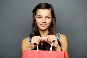 Portrait of happy brunette with paperbag looking at camera