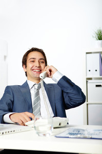 Portrait of happy businessman talking on phone in office