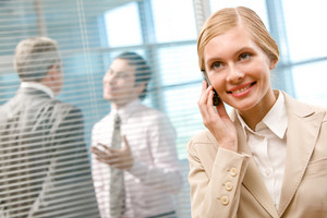 Portrait of happy businesswoman calling by cellphone on background of interacting men