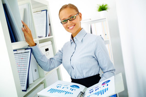Portrait of happy businesswoman looking for book on the shelf in office