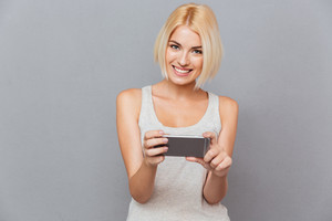 Portrait of happy charming young woman smiling and using smartphone over gray background