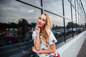Portrait of happy charming young woman standing outdoors