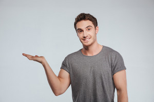 Portrait of happy cheerful young man holding copyspace on palm over white background