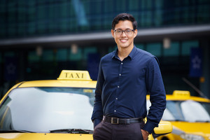 Portrait of happy chinese taxi driver leaning on yellow car with arms crossed, smiling and looking at camera