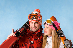Portrait of happy couple holding skis and communicating with each other