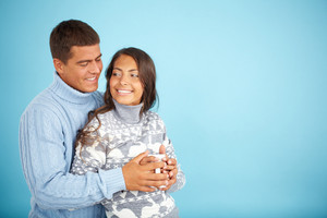 Portrait of happy couple in fashionable pullovers posing against blue background